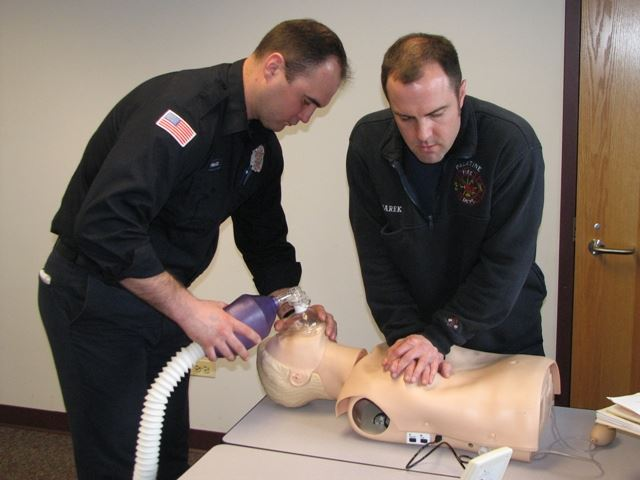 Firefighter / paramedics practice CPR on a training manikin.