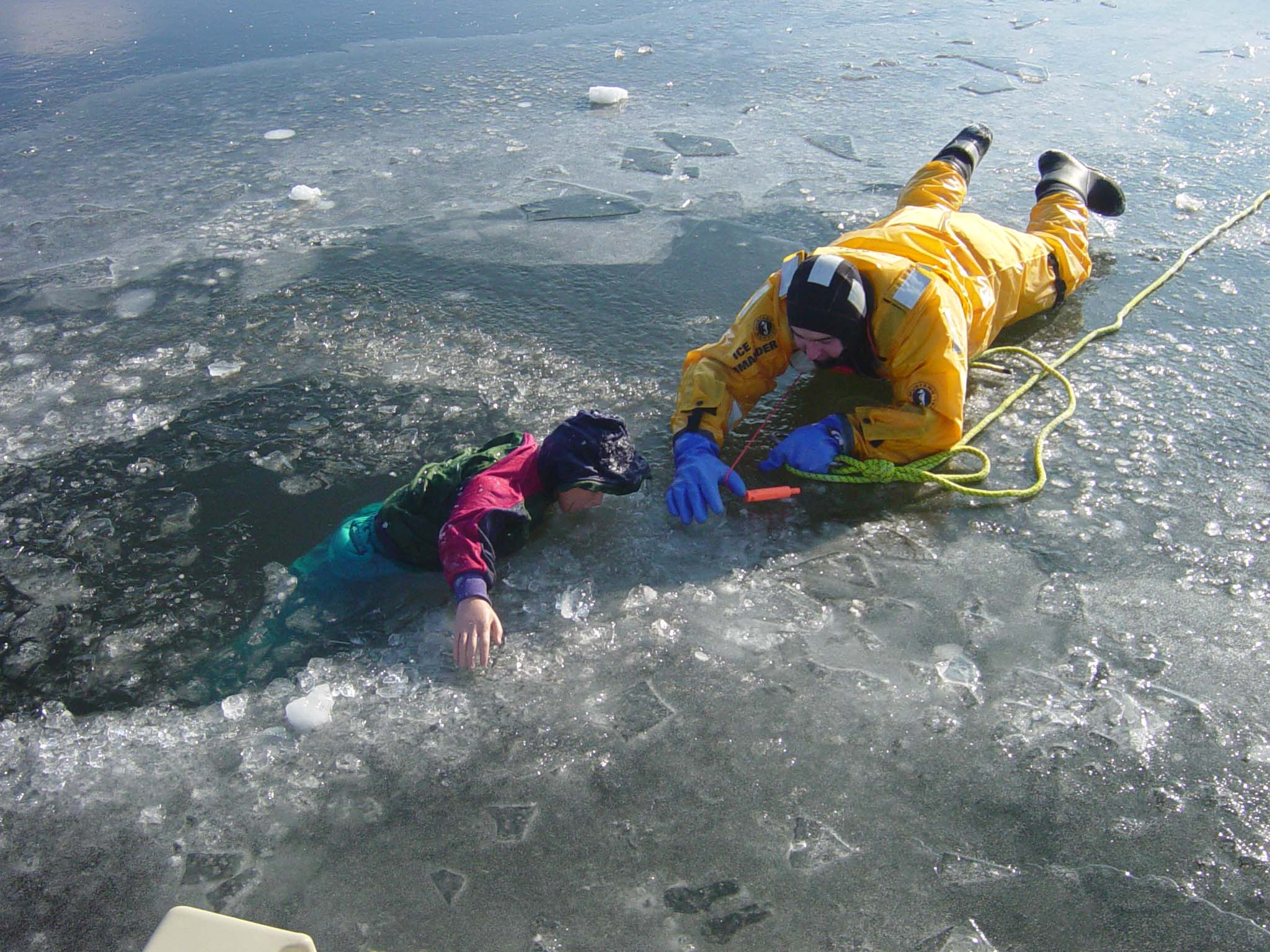 Firefighter practices ice rescue techniques with a child-size mannequin at a winter training drill.