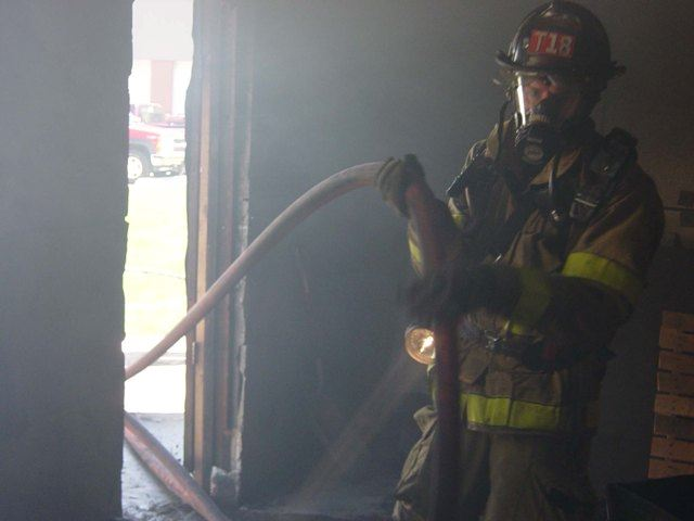 Firefighter advances hose line at a live fire training drill.
