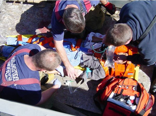 Firefighters practice medical techniques on a training mannequin during a medical / rescue training